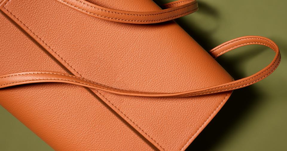 Moodbild einer hellbraunen Lederhandtasche vor olivgrünem Grund