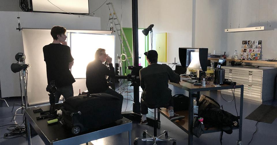 Ein Fotograf und zwei Assistenten arbeiten im Fotostudio.