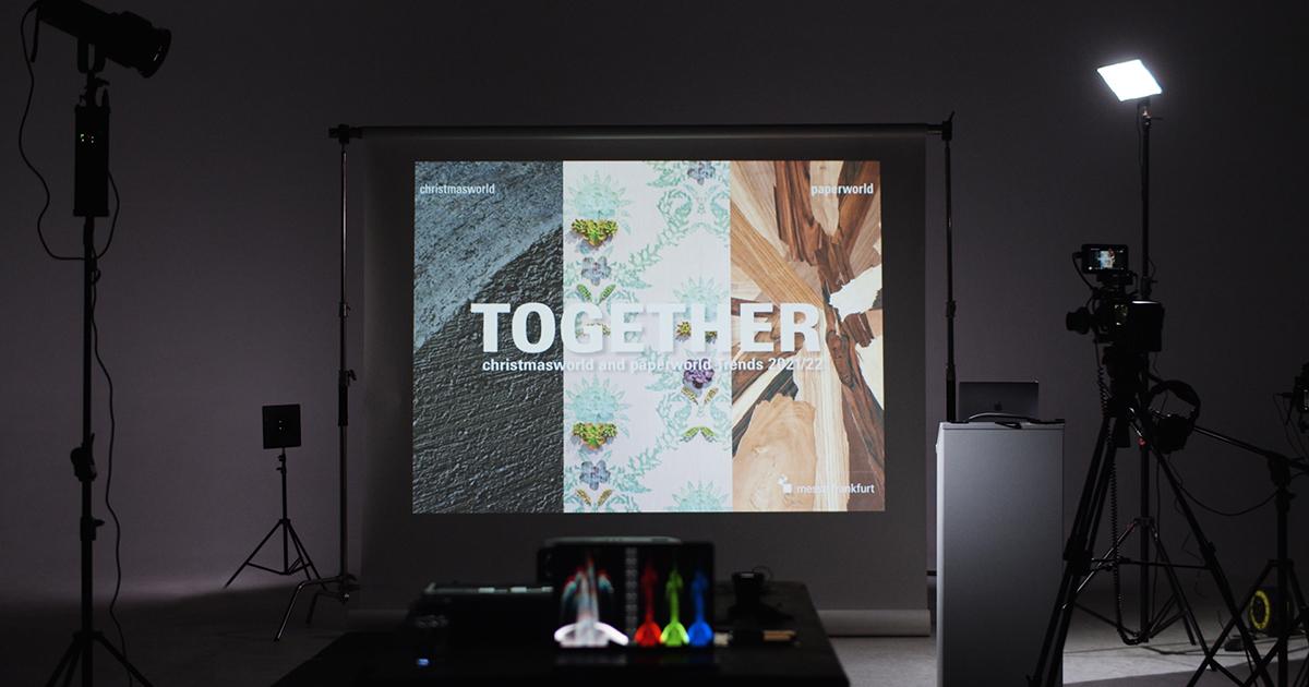 """Ein Blick hinter die Kulissen eines Studio-Settings mit einer Projektion, die den Schriftzug """"Together"""" zeigt"""