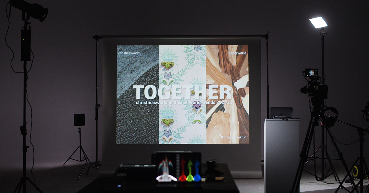 """A behind-the-scenes look at a studio set with a projection that reads """"Together"""""""