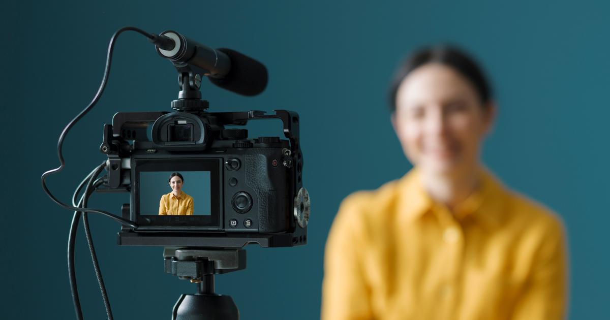 Ein weiblicher Videoblogger streamt mit einer digitalen Systemkamera.
