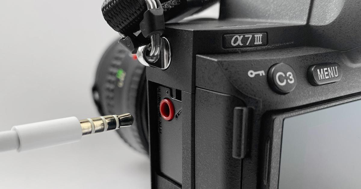 Eine 3,5mm-Klinke wird in den Mikrofoneingang einer Sony Alpha 7 III gesteckt.