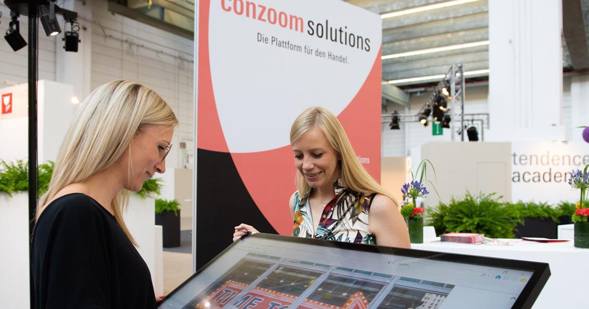 Zwei Frauen bedienen ein Touchpad von Conzoom Solutions, im Hintergrund ist Messegeschehen