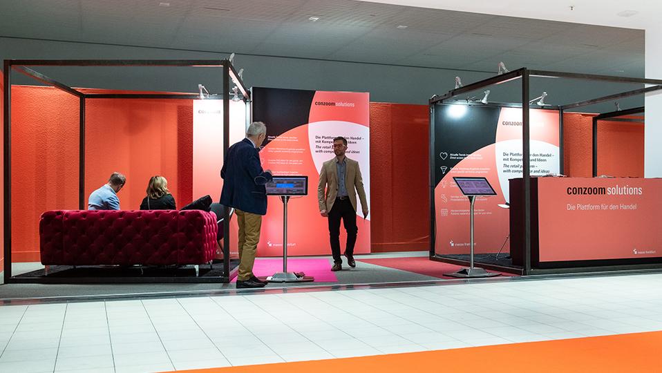 Die Lounge von Conzoom Solutions mit Theke, einem roten Sofa und zwei Touchbildschirme.