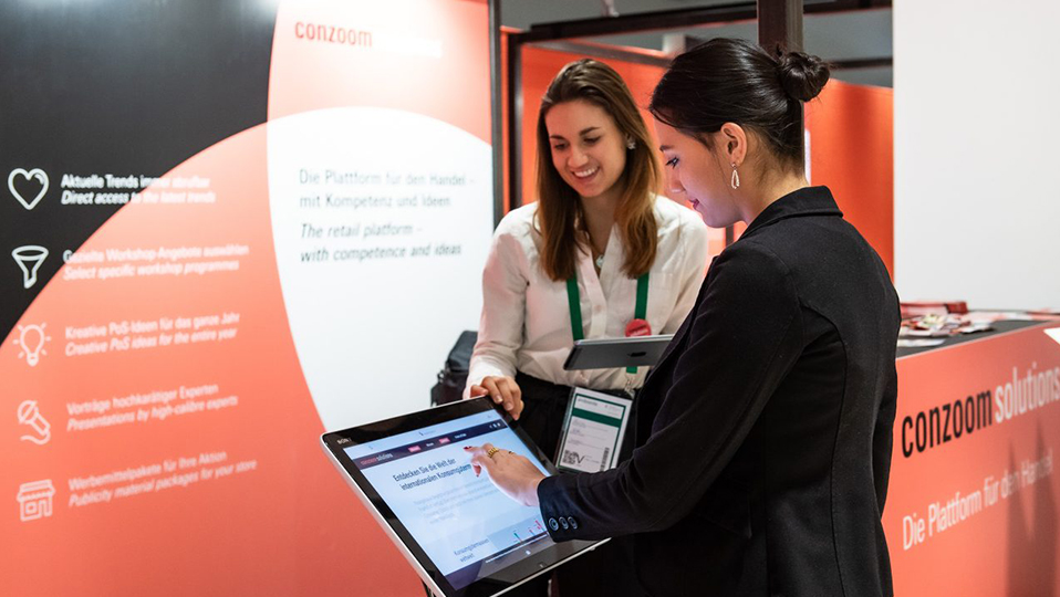 Zwei Frauen bedienen das Touchpad von Conzoom Solutions, im Hintergrund ist eine Theke und ein Plakat der Online-Plattorm
