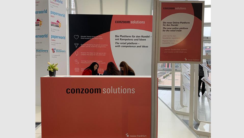 Zu sehen ist der Messestand von Conzoom Solutions mit einer Theke, einem Poster im Hintergrund und einem Aufsteller. Hinter der Theke sitzen 3 Frauen an einem Tisch