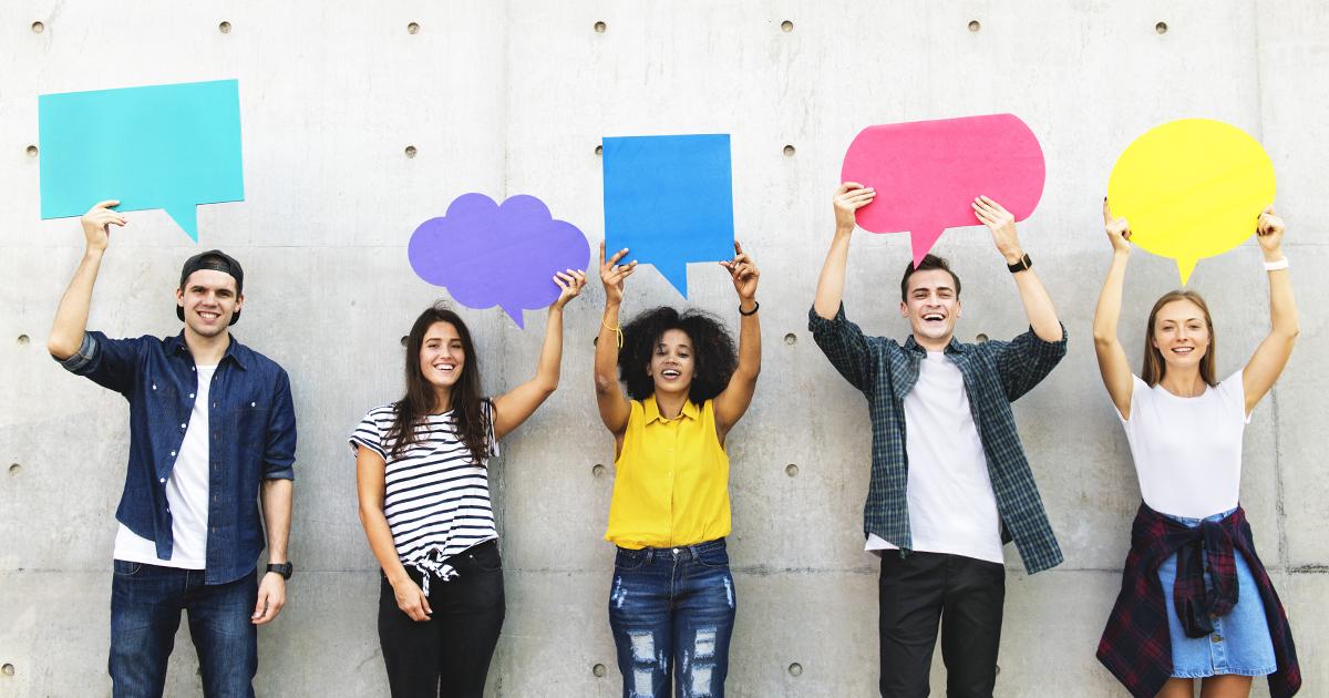 Junge Social-Media-Nutzer halten bunte Sprechblasen aus Papier in die Luft.