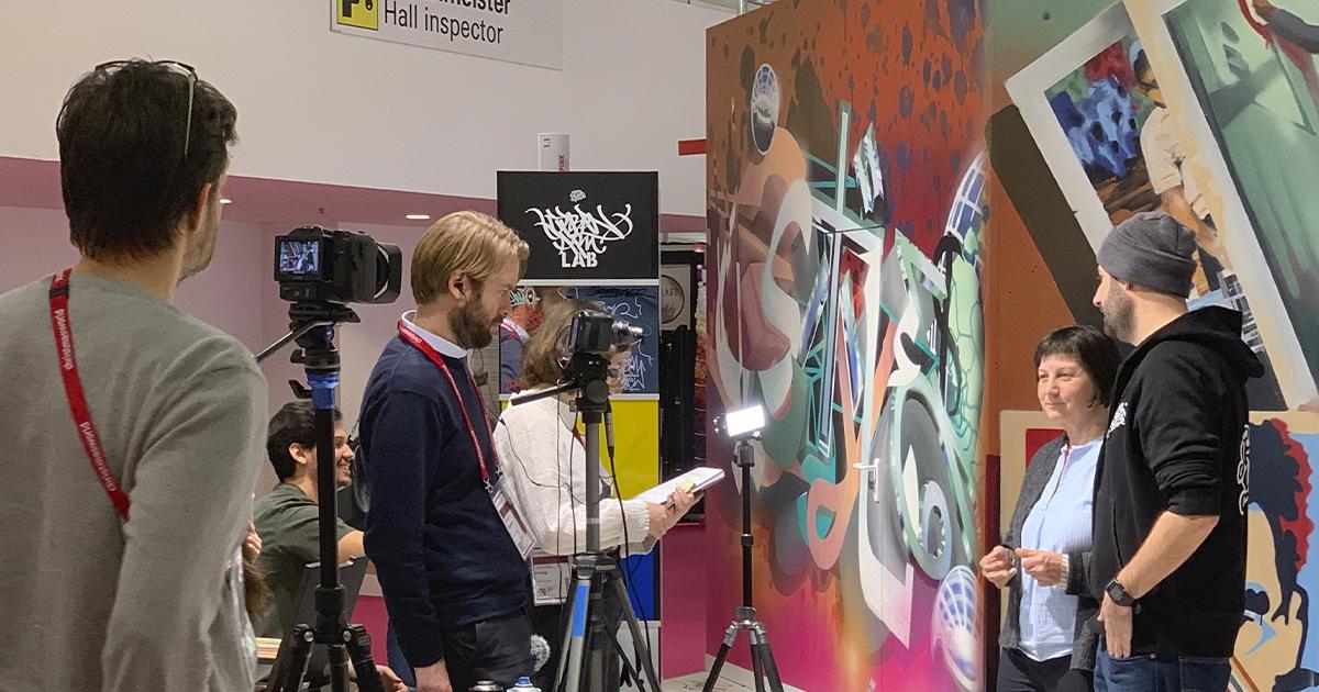 Eine Videocrew nimmt ein Interview an einem Messestand auf.